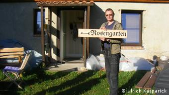 Ulrich Kasparick holding a sign to the rose garden at the church in Uckermark