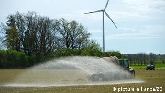Traktor verteilt Gülle auf Feld in Brandenburg