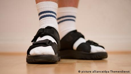 A close-up shot of a two feet in socks and sandals
