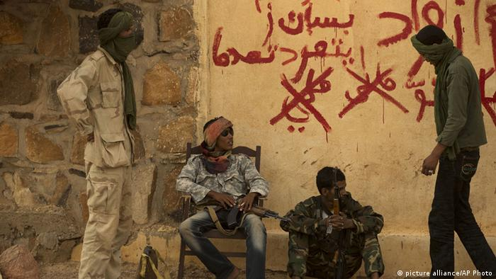 A symbolic photo from July 2013 showing rebels from the National Movement for the Liberation of the Azawad (NMLA) in Mali, standing guard outside the former governor's office, in Kidal-(AP Photo/Rebecca Blackwell, File)