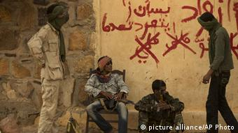 FILE - In this Friday, July 26, 2013 file photo, rebels from the National Movement for the Liberation of the Azawad (NMLA) stand guard outside the former governor's office, in Kidal, Mali. Malian soldiers and ethnic Tuareg separatist rebels clashed again in the northern desert town of Kidal early Monday, Sept. 30, 2013, a day after trading gunfire downtown in a battle that has raised fears about whether an unraveling peace accord could lead to protracted fighting in the region. (AP Photo/Rebecca Blackwell, File)