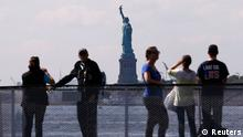 Tourists stand next to a sign announcing the closure of the Statue of Liberty, a U.S. National Park, due to the U.S. Government shutdown near the ferry dock to the Statue of Liberty in Battery Park in New York, October 1, 2013. The U.S. government began a partial shutdown on Tuesday for the first time in 17 years, potentially putting up to 1 million workers on unpaid leave, closing national parks and stalling medical research projects. REUTERS/Mike Segar (UNITED STATES - Tags: POLITICS BUSINESS TRAVEL)