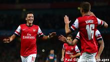 LONDON, ENGLAND - OCTOBER 01: Mesut Oezil #11of Arsenal is congratulated by teammate Aaron Ramsey #16 after scoring the opening goal during UEFA Champions League Group F match between Arsenal FC and SSC Napoli at Emirates Stadium on October 1, 2013 in London, England. (Photo by Paul Gilham/Getty Images) Erstellt am: 01 Okt 2013