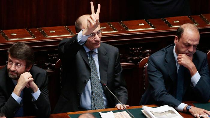 Italy's Prime Minister Enrico Letta (C), flanked by Interior Minister Angelino Alfano (R) and Democratic Party (PD) member Dario Franceschini, gestures after asking for a possible call for a confidence vote immediately at the Lower house of the parliament in Rome, October 2, 2013. REUTERS/Remo Casilli (ITALY - Tags: POLITICS)