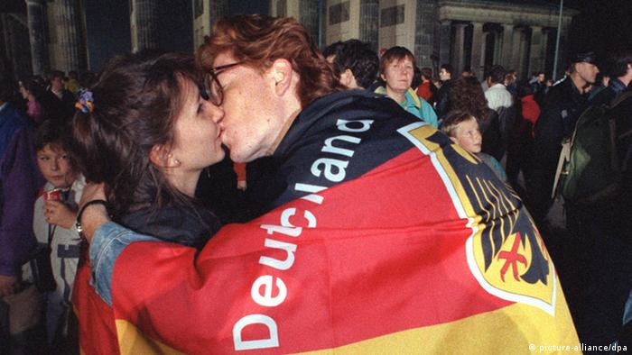 Two people wrapped in a German national flag kissing in front of the Brandenburg Gate (picture-alliance/dpa)