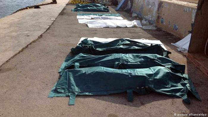 epa03893732 A row of dead bodies are covered with sheets at the port of Lampedusa, Italy, 03 October 2013. According to Italian port authorities, at least 82 bodies have been recovered off the Italian coast after a ship carrying migrants sank near the southern island of Lampedusa. The ship, which was believed to be carrying hundreds of migrants from Somalia and Eritrea, suffered extensive damage as it approached the smaller island of Conigli. EPA/NINO RANDAZZO BEST QUALITY AVAILABLE. +++(c) dpa - Bildfunk+++