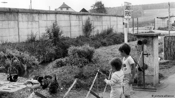 Kinder beobachten am 31.05.1988 Enten an der Zonengrenze in Mödlareuth. Im Hintergrund rechts ist das Loch in der Mauer zu sehen.