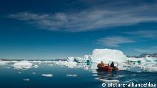 Ein kleines Boot, gesteuert von einem Inuit, mit Touristen fährt zwischen Eisbergen im Sermilik-Eisfjord im Ammassalik-Distrikt nahe der Jägersiedlung Tiniteqilaaq in Ostgrönland, Grönland, Dänemark, aufgenommen am 17.07.2012. Foto: Patrick Pleul