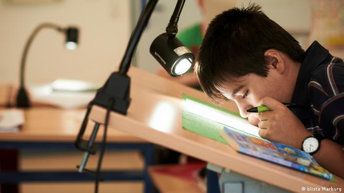 Ein blinder Schüler der Blindenstudienanstalt (Blista) in Marburg sitzt an seinem Pult und liest einen Blindentext im Deutschunterricht. Copyright: Blista Marburg
