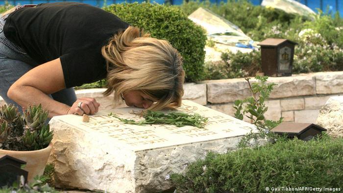 Eine Israelin küsst während einer Trauerzeremonie den Grabstein eines gefallenen Soldaten. - Foto: AFP PHOTO/GALI TIBBON (GALI TIBBON/AFP/Getty Images)
