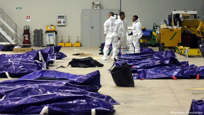 epa03894672 Bodies retrieved from the sea are pictured inside a hangar in Lampedusa, Italy, 03 October 2013. A boat carrying about 500 people from North Africa caught fire before reaching the Italian island of Lampedusa on 03 October. Rescuers recovered 82 bodies and reported at least 250 people were still missing. EPA/FRANCO LANNINO +++(c) dpa - Bildfunk+++