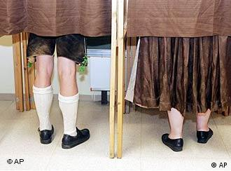 A couple in traditional Bavarian costume stand in polling booths