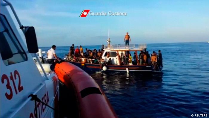 A still image taken from video released on October 4, 2013 by the Italian Coastguard shows migrants rescued from the water off the southern Italian island of Lampedusa on Thursday October 3, 2013. Italian rescue workers have pulled 111 bodies from the migrant boat that sank off the island of Lampedusa on Thursday and expect to recover more than a hundred more from the submerged wreck, a coastguard official said on Friday. Footage taken October 3, 2013. REUTERS/Italian Coast Guard/Handout via Reuters (ITALY - Tags: DISASTER) ATTENTION EDITORS - THIS IMAGE WAS PROVIDED BY A THIRD PARTY. FOR EDITORIAL USE ONLY. NOT FOR SALE FOR MARKETING OR ADVERTISING CAMPAIGNS. THIS PICTURE IS DISTRIBUTED EXACTLY AS RECEIVED BY REUTERS, AS A SERVICE TO CLIENTS. MANDATORY CREDIT