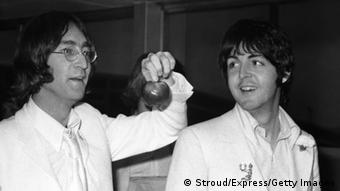 Beatles John Lennon and Paul McCartney at London Airport after a trip to America to promote their new company Apple Corps, 16th May 1968. They are both dressed all in white and carrying apples. (Photo by Stroud/Express/Getty Images)