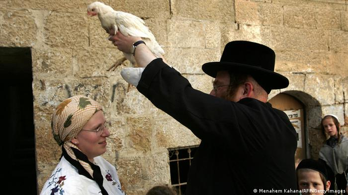 An ultra-orthodox Jew swings a chicken above his wife's head during the Kaparot ceremony