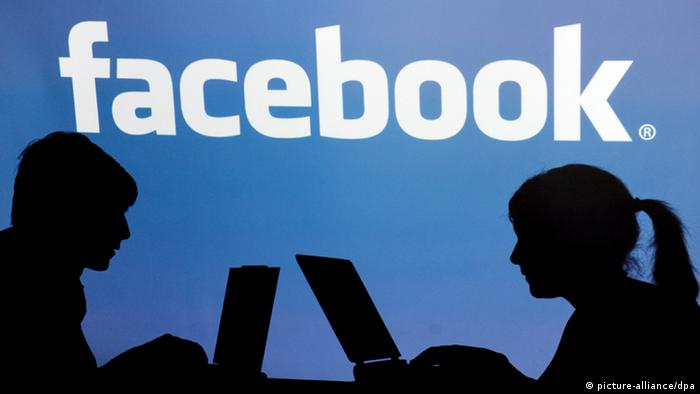 Teens using laptops silhouetted against Facebook logo