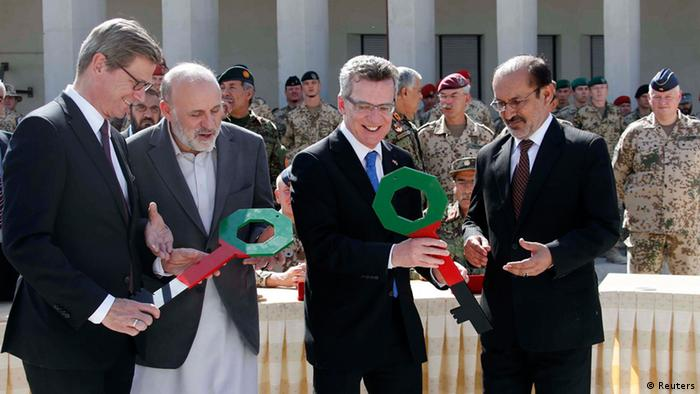 German Foreign Minister Guido Westerwelle (back row 2nd L-2nd R), German Defence Minister Thomas de Maiziere, Afghan Interior Minister Mohammad Omar Daudzai, and Afghan Deputy Defence Minister Enayatullah Nazari watch as German and Afghan Army senior officials sign documents during the handover ceremony of a German base to the Afghan armed forces in Kunduz October 6, 2013. Soldiers of the German contingency of the International Security Assistance Force (ISAF) withdrew from their base in Kunduz and the camp will be used by the Afghan National Army (ANA) and the Afghan National Civil Order Police (ANCOP). REUTERS/Fabrizio Bensch (AFGHANISTAN - Tags: CIVIL UNREST MILITARY POLITICS)