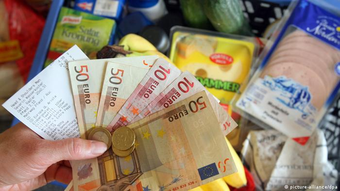 Hand holding euro banknotes, with food items in the background Photo: Jens Büttner +++(c) dpa - Report+++