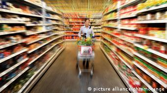 Frau kauft in einem Supermarkt Lebensmittel ein. (Foto: picture alliance/chromorange)