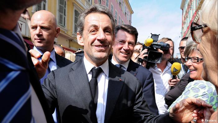 Former French president Nicolas Sarkozy (C) greets well-wishers as he arrives for a lunch with the Mayor of Nice, Christian Estrosi (R) and UMP political party members in Nice September 27, 2013. REUTERS/Olivier Anrigo (FRANCE - Tags: POLITICS)