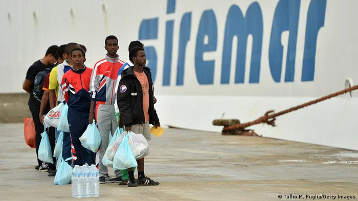 African migrants hold plastic bags full of belongings as they wait to board a ship to Italy