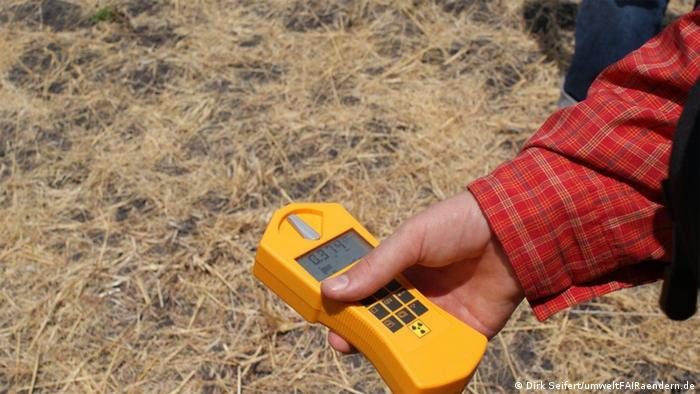 An off-camera man wearing a red shirt holds a yellow geiger counter that shows the level of radioactivity in an outdoor, dusty setting Photo: Dirk Seifert