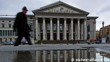ARCHIV - Ein Fußgänger läuft am 24.01.2012 an der Staatsoper in München (Oberbayern) vorbei, die sich in einer Wasserpfütze am Boden widerspiegelt. 1963 wurde das Theater nach dem 2. Weltkrieg wiedereröffnet. Foto: Peter Kneffel/dpa +++(c) dpa - Bildfunk+++