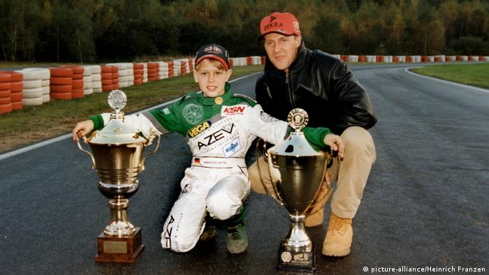 A young Sebastian Vettel, in 1999, holding go-kart trophies with Michael Schumacher on the Kerpen kart track owned by the Schumacher family. (picture-alliance/Heinrich Franzen)