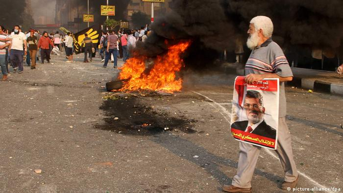 epa03899736 An Egyptian supporter of ousted President Morsi holds a poster depicting him as he walks past a fire during clashes on the day the country celebrates the 40th anniversary of the 1973 Arab-Israeli war, in the Dokki part of Giza, near Cairo, Egypt, 06 October 2013. Crowds supporting the Egyptian military gathered in central Cairo's Tahrir Square to mark Army Day on 06 October. Meanwhile an alliance led by Morsi's Muslim Brotherhood called on followers to march to Tahrir Square later the same day. According to media reports, 28 people have been killed in clashes across Egypt on 06 October, the Health Ministry said. EPA/AHMED OTAIFY
