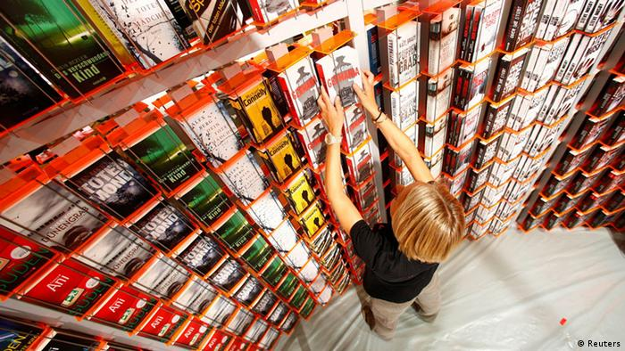A woman sorts books at a booth during preparations for the upcoming book fair in Frankfurt, October 8, 2013. The world's largest book fair runs from October 9 to October 13 and features the literature of Brazil as its guest of honour. REUTERS/Ralph Orlowski (GERMANY - Tags: MEDIA BUSINESS)
