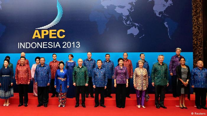 Leaders with their spouses wearing Indonesian traditional clothes at APEC Summit.