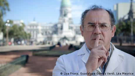 Argentine surgeon German Cardoso in front of the congress building in Buenos Aires. He is pressing his index finger to his lips in a gesture of silence. (Copyright: Lisa Franz, Guadalupe Gómez Verdi, Léa Meurice)