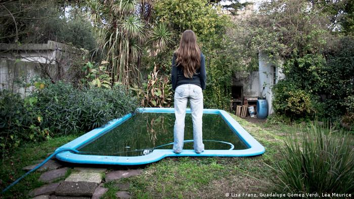 Mara stands by the pool in her family's garden with her back to the camera. (Copyright: Lisa Franz, Guadalupe Gómez Verdi, Léa Meurice)