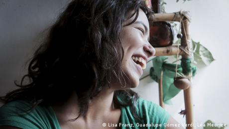 A portrait of Eluney laughing, with a plant in the background. 