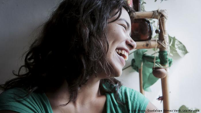 A portrait of Eluney laughing, with a plant in the background.  (Copyright: Lisa Franz, Guadalupe Gómez Verdi, Léa Meurice)