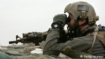 A navy seal looks through a pair of binoculars