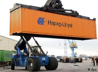 A shipping container with the name Hapag-Lloyd written on it is being lifted