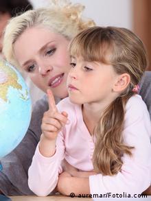 Eine Mädchen sitzt mit erhobenem Zeigefinger vor einem Globus und erkl#ärt ihrer Mutter etwas