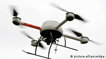 A quadcopter drone with four rotor blades flies against a white backdrop. Photo: Jochen Lübke