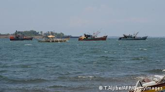 TO GO WITH AFP STORY 'PHILIPPINES-CHINA-US-MARITIME-MILITARY-DIPLOMACY-FISHING-FOCUS' by Mynardo Macaraig Fishing boats (2nd L, and at left) also locally known as 'mother boats' which are used to transport fish caught around Scarborough shoal, are anchored off Santa Cruz bay, Zambales province, north of Manila, facing south China sea (back) on May 10, 2012, after arriving a day before from the shoal. For years Filipino and Chinese fishermen peacefully shared the rich harvests around a tiny South China Sea shoal, but today threats, harassment and fear have replaced ocean comradery. AFP PHOTO/TED ALJIBE (Photo credit should read TED ALJIBE/AFP/GettyImages)