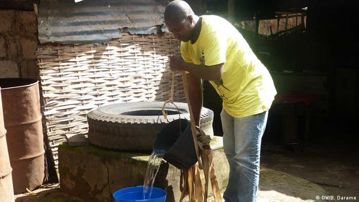 Mann in Bissau holt Wasser aus dem Brunnen