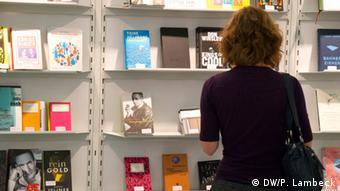 Bücherregal: Eine Frau vor einem Bücherregal mit Büchern, die für den Preis Die schönsten deutschen Bücher 2013 nominiert waren