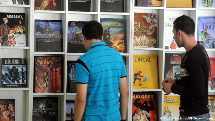 Men look at books during the 55th international comic strip festival in Algiers on October 6, 2011. AFP PHOPTO FAROUK BATICHE (Photo credit should read FAROUK BATICHE/AFP/Getty Images)