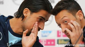 COLOGNE, GERMANY - OCTOBER 10: Sami Khedira (L) and Mesut Oezil of Germany talk during a press conference ahead of the FIFA 2014 World Cup Qualifier match against Republic of Ireland on October 10, 2013 in Cologne, Germany. (Photo by Juergen Schwarz/Bongarts/Getty Images)