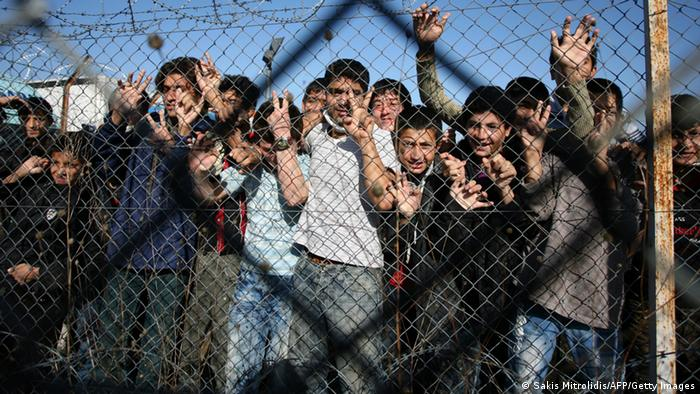 Immigrant minors peer out through the fence of an immigrant detention center in the village of Filakio, on the Greek-Turkish border, upon the arrival there of the Frontex Rapid Border Intervention Teams (RABITs) and EU officials on November 5, 2010. (Photo: SAKIS MITROLIDIS/AFP/Getty Images)
