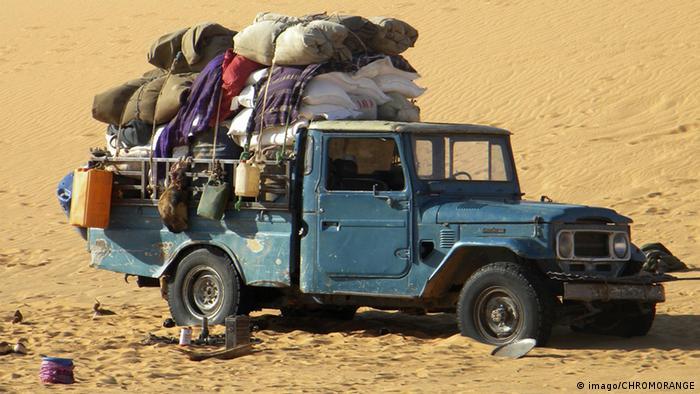 A truck in the desert laden with migrants' belongings