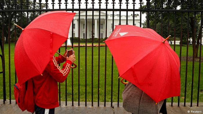 Two people with red umbrellas in front of white house.