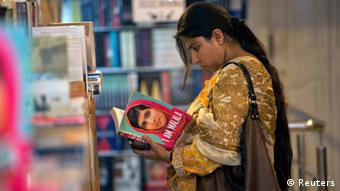 A woman browses a copy of Malala Yousufzai's book I am Malala at a book store in Islamabad October 8, 2013. REUTERS/Mian Khursheed (PAKISTAN - Tags: MEDIA POLITICS)
