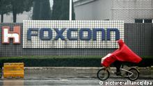 epa03408560 (FILE) A file photograph showing a cyclist riding past a Foxconn factory complex located in Kunshan, Jiangsu Province, China, 31 March 2012. Media reports on 24 Spetember 2012 state that Taiwan-based Foxconn Technology, a major supplier for Apple stopped work at the factory in Taiyuan, northern China after a mass fight started between workers. Foxconn reported that a 'personal dispute' led to an incident involving near 2,000 workers, leaving 40 people injured. EPA/Qilai Shen *** Local Caption *** 50284106 pixel