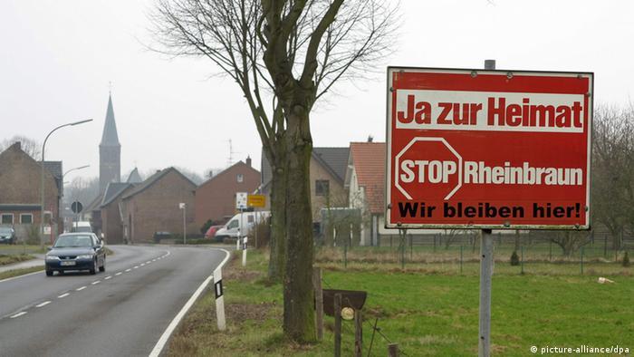 Ein Schild mit der Aufschrift: 'Ja zur Heimat Stop Rheinbraun, wir bleiben hier!! an der Landstrasse vor dem Ortseingang von Keyenberg.